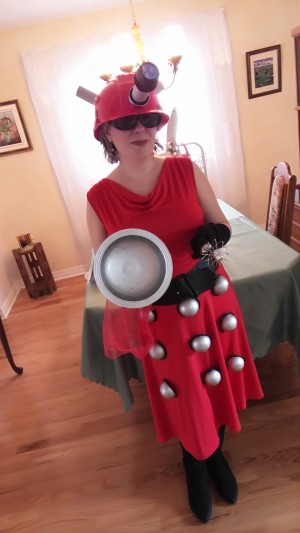 ID: Me, wearing my fashionista dalek costume. It's a red sleeveless dress with a black belt and little silber dalek hemispheres down the skirt in three rows. I'm holding a silver plunger and a whisk, and have a red construction helmet made to look like the head of a dalek.