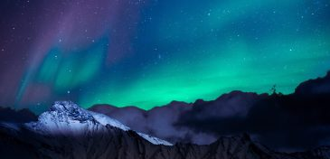 ID: Night sky over mountains. Something resembling northern lights makes the sky streak with green and purple. A snowy hilltop is highlighted in the moonlight.
