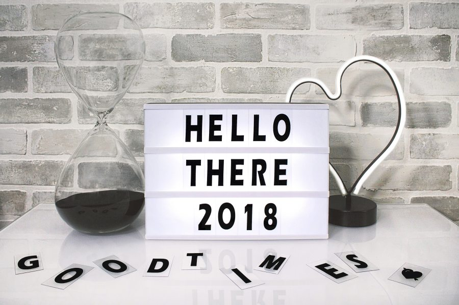 "ID: Grey brick wall and light grey table. A sign on the table reads: Hello there 2018 and scattered on the table are the letters that spell ""Good times."" There's an hourglass to the left of the sign and a heart lamp sculpture to the right."