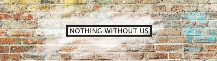 "ID: Graffiti wall with black border surrounding the words ""Nothing without Us."""