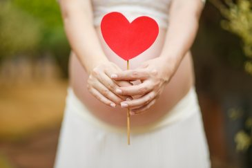 ID: Pregnant human holding a red paper heart in front of their belly.