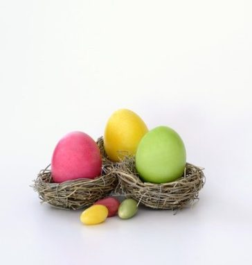 Pink, yellow, and green easter eggs sitting in their own nests.