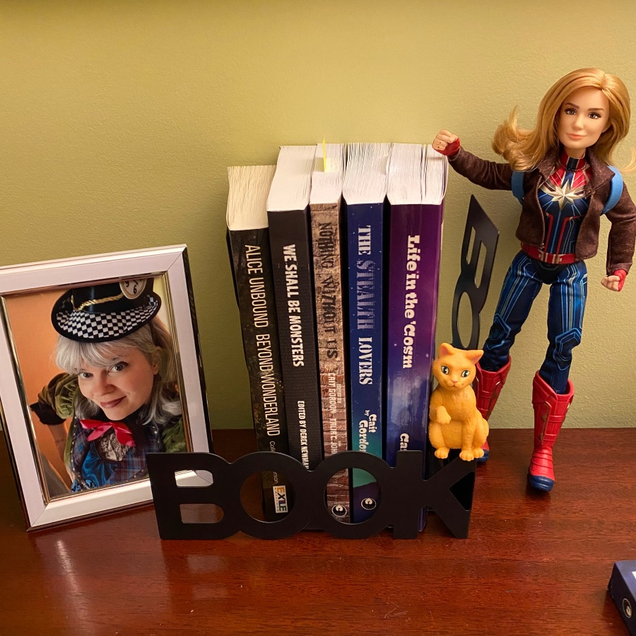 "Photo of me dressed as the Mad Hatter, then five books: Alice Unbound Beyond Wonderland, We Shall Be Monsters, Nothing Without Us, The Stealth Lovers, Life in the 'Cosm. And a figure of Captain Marvel and her ""cat."""