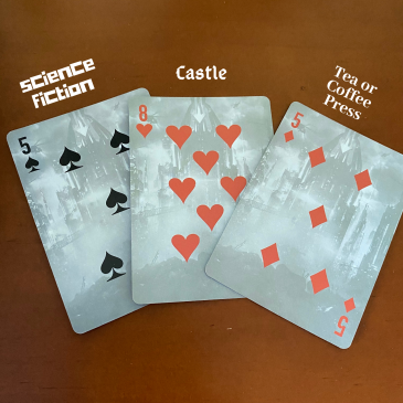 Three cards on a table: 5 of spades (science fiction), 8 of hearts (castle), and the 5 of diamonds (tea/coffee press.)