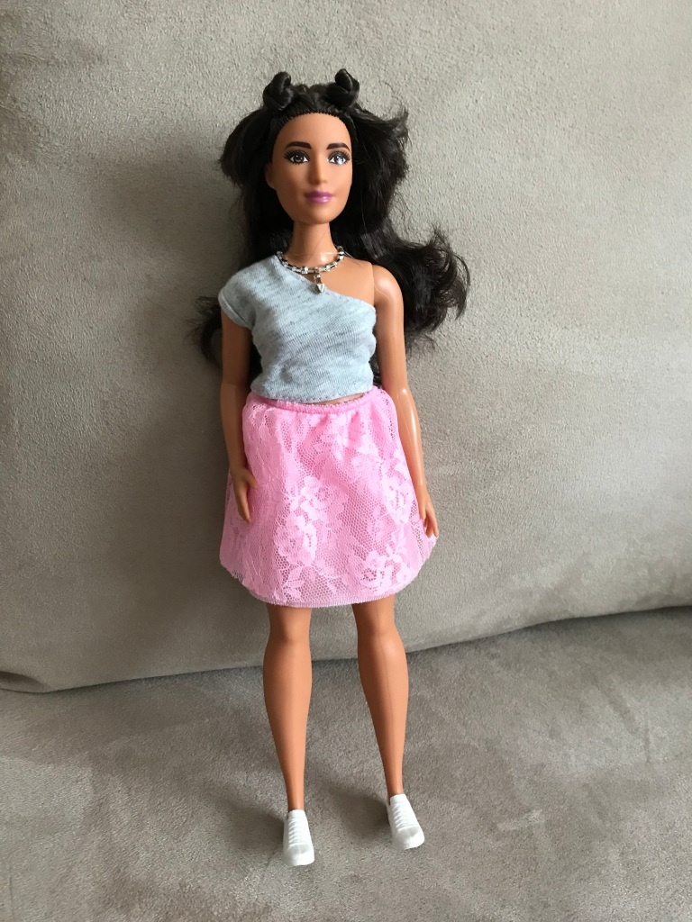 ID: Brunette Barbie with a grey one-shoulder top and pink skirt. Her hair is worn long in the back with two tiny buns on top.