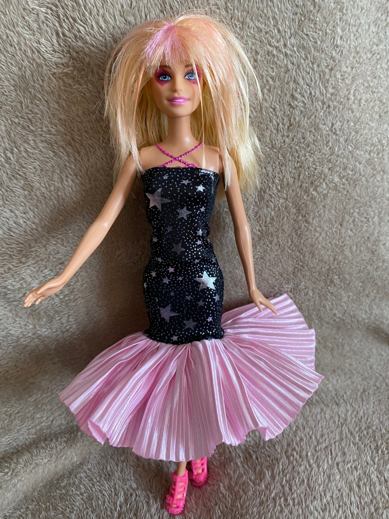 ID: Barbie as Jem from Jem and the Holograms. Blonde and pink hair is cut into 80s rocker style. Pink diamond makeup shapes surround her eyes. Her slim strapless dress is black with silber stars, with a pink ruffled bottom that bows out like a mermaid cut.