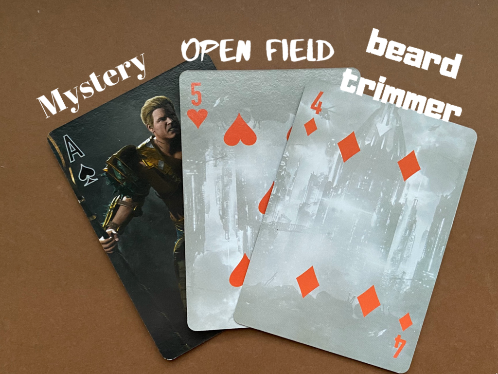 ID: Three cards. Ace of spades (mystery), 5 of hearts (open field), and 4 fo diamonds (beard trimmer).