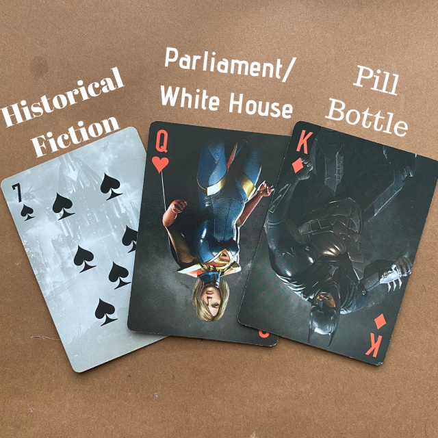 ID: Card draw—7 of spades (historical fiction), Queen of hearts (Parliament/White House gathering), and King of diamonds (pill bottle).