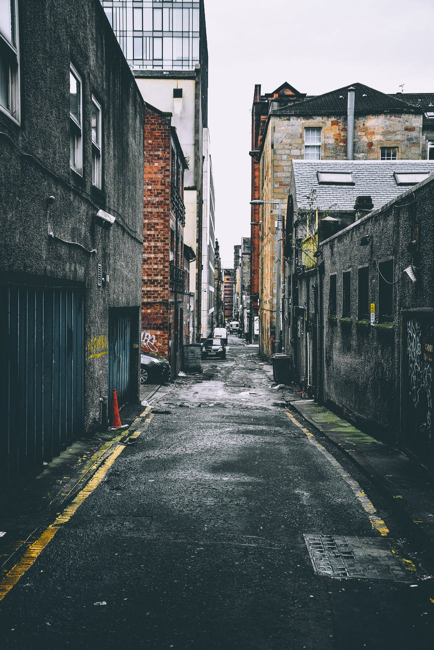 ID: gray and brown buildings on each side of an alleyway