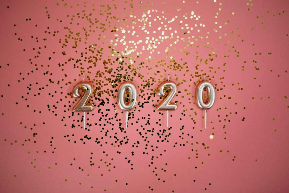 ID: A salmon pink background with gold glitter and gold unlit candles in the shape of 2020