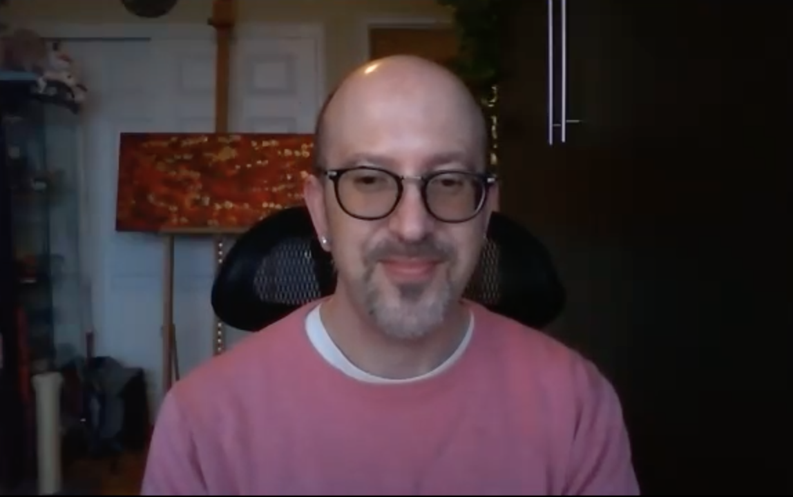 ID: Jamieson Wolf, wearing a pink sweater, sitting in his office in front of an abstract painting in oranges.