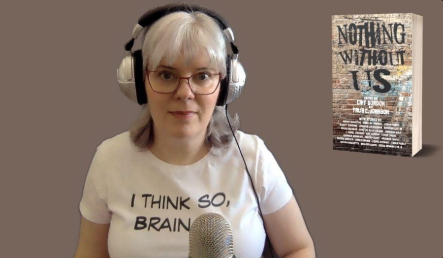"ID: I'm at my desk. Zoom background of a soft brown with the cover of Nothing Without Us. I'm wearing my silver and black headphones and a white tee that says, ""I think so, Brain..."""